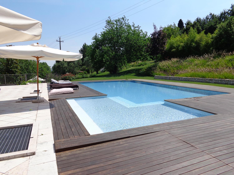 Primo piano piscina a sfioro isotermica e antisismica con scala angolare bicolore. Piscina autopulente con bordo sfioratore in legno per fondersi con la campagna circostante.