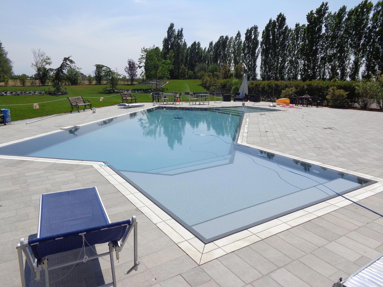 Primo piano zona relax angolare con scalini interni. Questa piscina a sfioro è caratterizzata da un doppio ingresso per favorire la balneazione dei clienti del ristorante.