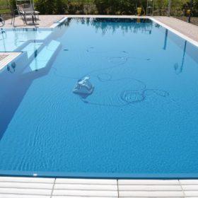 Robot piscina Dolphin Maxi durante la pulizia di una piscina a sfioro senza vasca di compenso ad altissima resa. Piscina adatta ad ospitare il robot grazie agli scalini di 50cm.