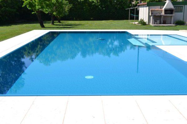 Vista frontale di una piscina isotermica ad alto rendimento energetico. Piscina dotata di impianto di filtrazione a sabbia di vetro e luci a led a bassi consumi.