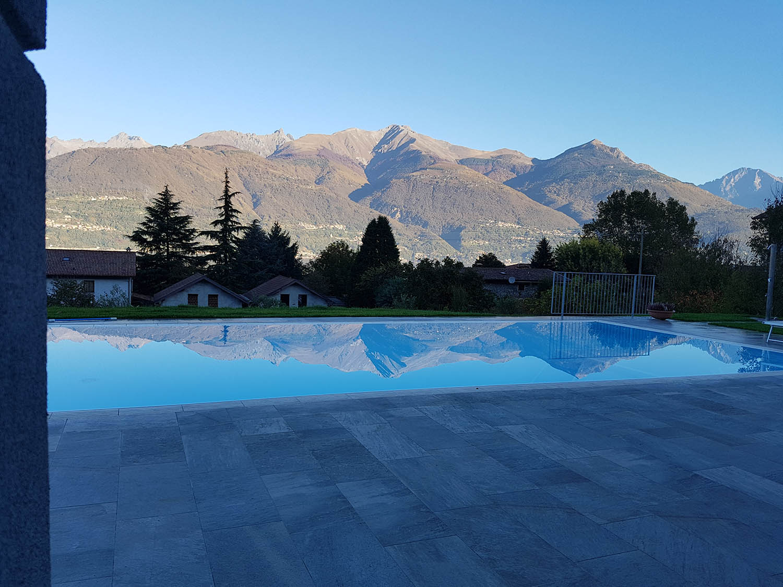 Montagne riflesse sulla perfetta superficie di una piscina a sfioro senza vasca di compenso Zavatti