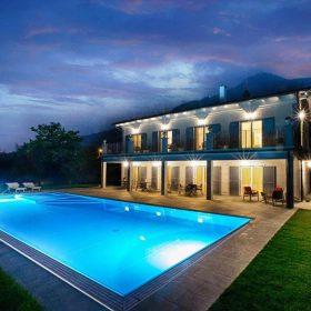 Vista notturna di una piscina a sfioro con bordo in pietra naturale ricostruita.