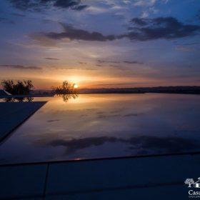 Tramonto riflesso sulla superficie di una piscina a sfioro isotermica ad alto risparmio energetico.