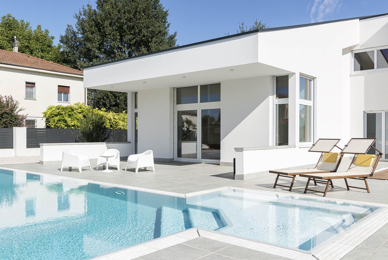 Dettaglio spiaggia piscina a sfioro Zavatti con griglia in pietra ricostruita bianca.