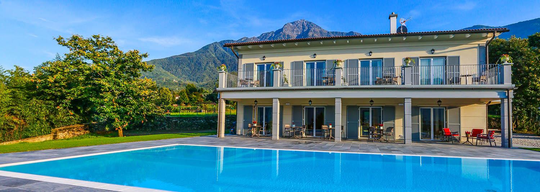 Panoramica di una piscina a sfioro con zona relax interna e rivestimento bianco.