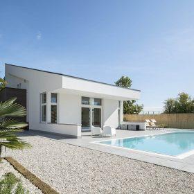 Piscina a sfioro autopulente perfettamente integrata con il design di questa abitazione ad alto risparmio energetico