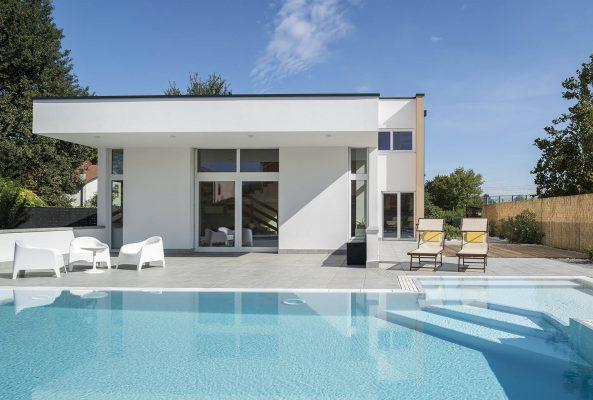Vista zona relax di una piscina a sfioro senza vasca di compenso con rivestimento grigio chiaro.