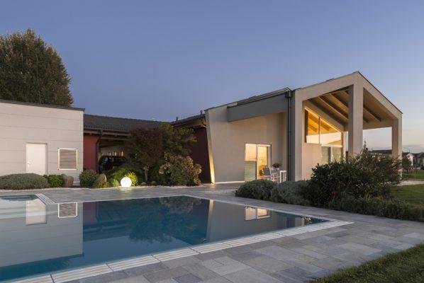 Casa riflessa su piscina a sfioro senza vasca di compenso con griglia in pietra naturale.