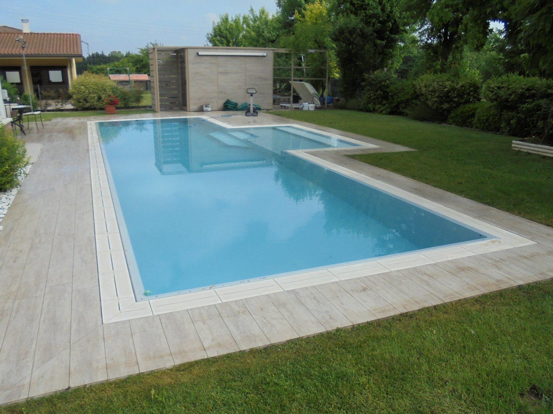 Vista totale piscina a sfioro con zona relax centrale realizzata con la qualità del Made in Italy