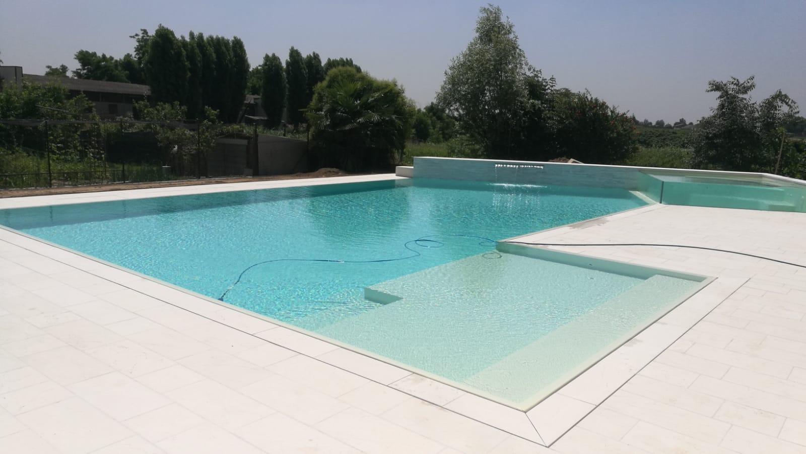 Panoramica piscina a sfioro senza vasca di compenso con bordo sfioratore e rivestimento bianco