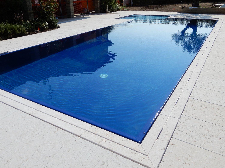 Piscina con rivestimento deep blue e griglia in pietra ricostruita bianca ad una fessura