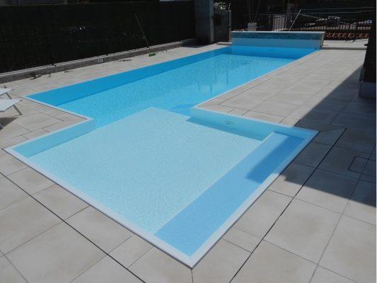Piscina a basso consumo energetico con cascata ed ampia zona relax realizzata con rivestimento antiscivolo