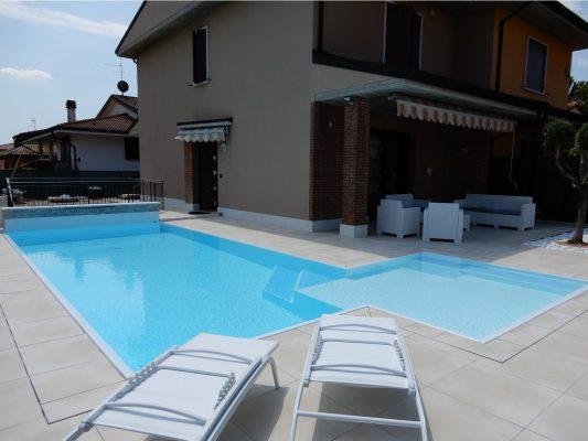 Vista totale di una piscina a sfioro autopulente con ingresso angolare e rivestimento completamente bianco