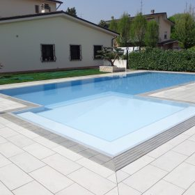 Primo piano zona relax di una piscina a sfioro rifinita con griglia in pietra naturale grigia
