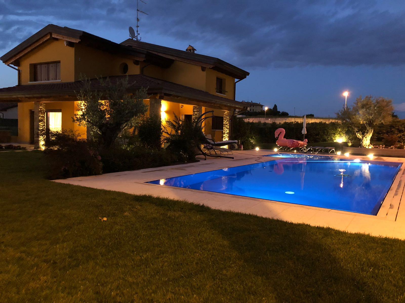 Atmosfera a bordo piscina con rivestimento blu e lamapde a LED a basso consumo energetico