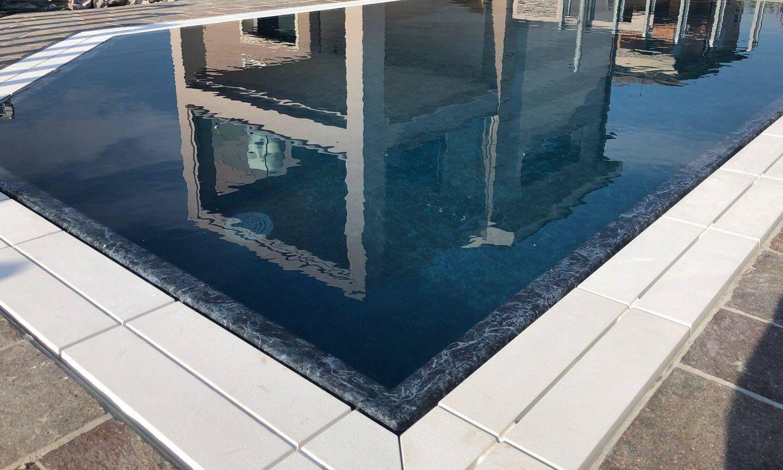 Dettaglio liner PVC nero marmorizzato, in contrasto con la griglia in pietra naturale bianca