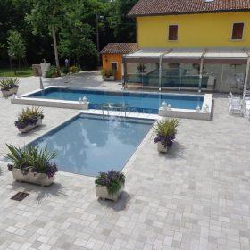 Panoramica piscina a sfioro con ampia zona relax realizzata completamente su misura