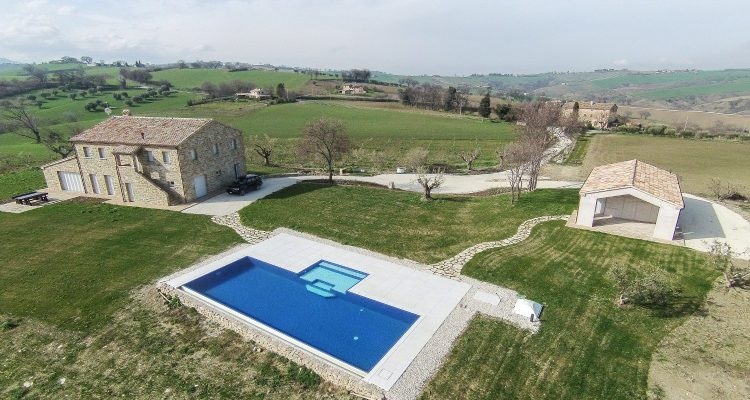 Vista dall'alto di una piscina con rivestimento bicolore immersa nel verde delle colline