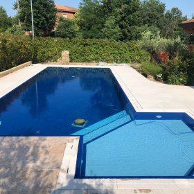 Vista frontale piscina con rivestimento blu intenso in contrasto con i gradini e la griglia di colore chiaro
