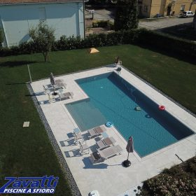Vista completa piscina a sfioro senza vasca di compenso con bagnasciuga centrale