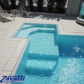 Bagnasciuga di design di una piscina a sfioro con bordo a scomparsa e rivestimento grigio