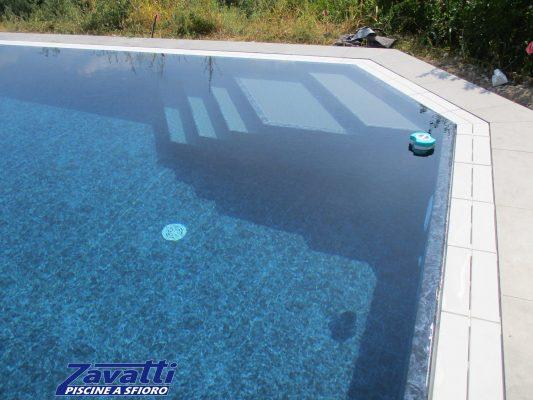 Dettaglio piscina sfioro con rivestimento marmorizzato e scala bicolore interna