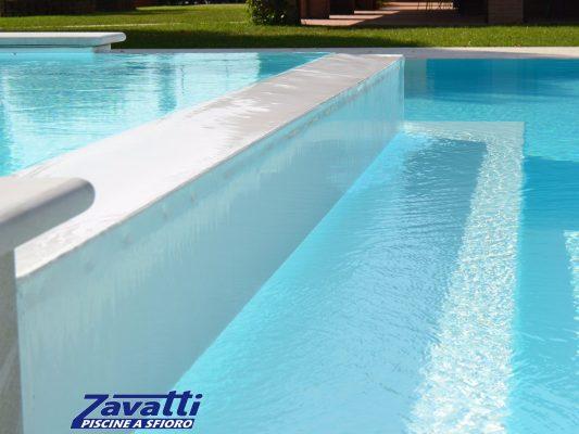 Dettaglio scalini piscina a sfioro con rivestimento bianco
