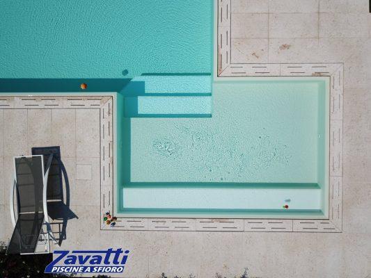 Dettaglio zona d'ingresso di una piscina a sfioro Zavatti con rivestimento bianco