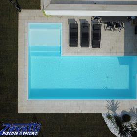 Foto aerea piscina a sfioro senza vasca di compenso con bordo sfioratore a scomparsa e rivestimento bianco