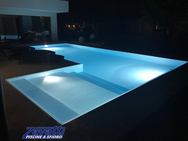 Piscina con bordo sfioratore a scomparsa e rivestimento bianco illuminata da lampade LED a basso consumo energetico