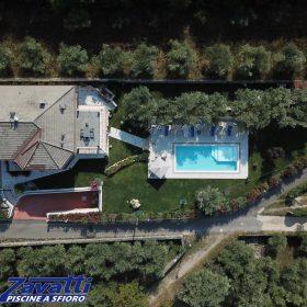 Ripresa aerea da drone di una piscina a sfioro Zavatti immersa nel verde