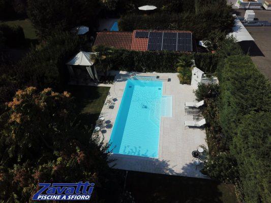 Vista aerea di una piscina a sfioro antisismica e ad altissimo risparmio energetico. Rivestimento bianco e scalinata centrale a gradoni trapezioidali