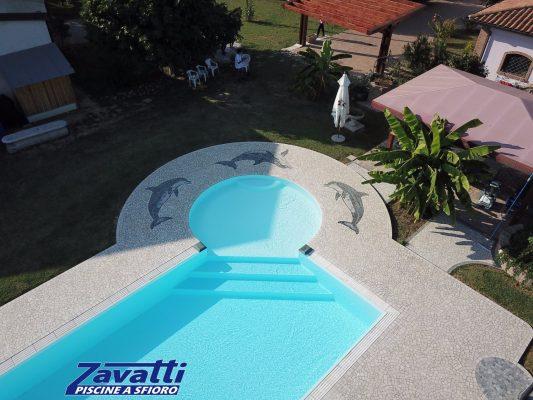 Vista aerea piscina a sfioro con bagnasciuga circolare angolare