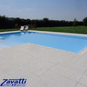 Vista completa di una piscina a sfioro autopulente Zavatti rifinita con griglia in pietra naturale bianca a una fessura
