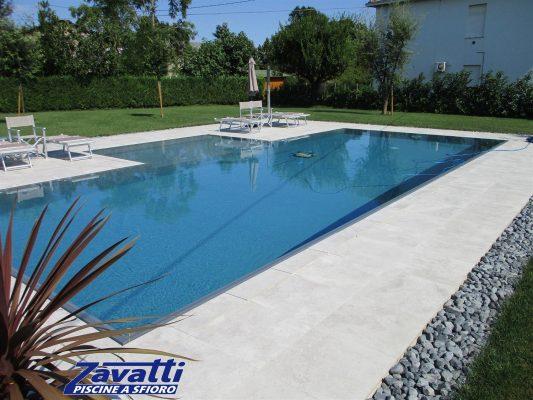 Vista completa piscina a sfioro con rivestimento grigio ad alta pigmentazione