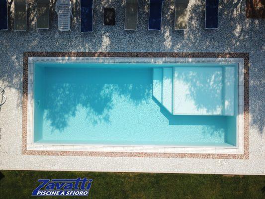Vista dall'alto di una piscina a sfioro Zavatti con griglia in pietra ricostruita bianca e zona relax interna