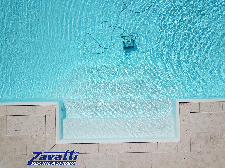 Vista dall'alto ingresso piscina con scalini trapezioidali e rivestimento pvc antiscivolo bianco