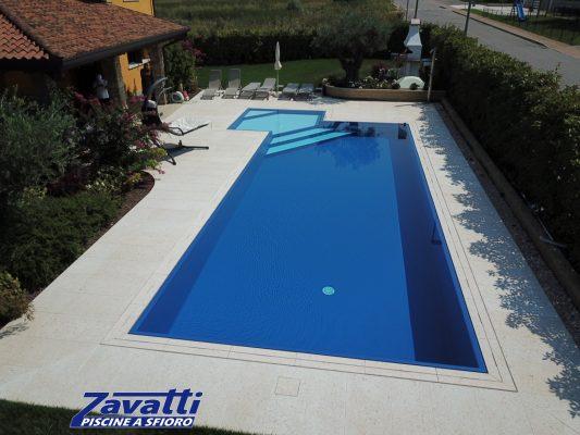 Vista frontale di una piscina a sfioro senza vasca di compenso costruita con casseri Easyblok