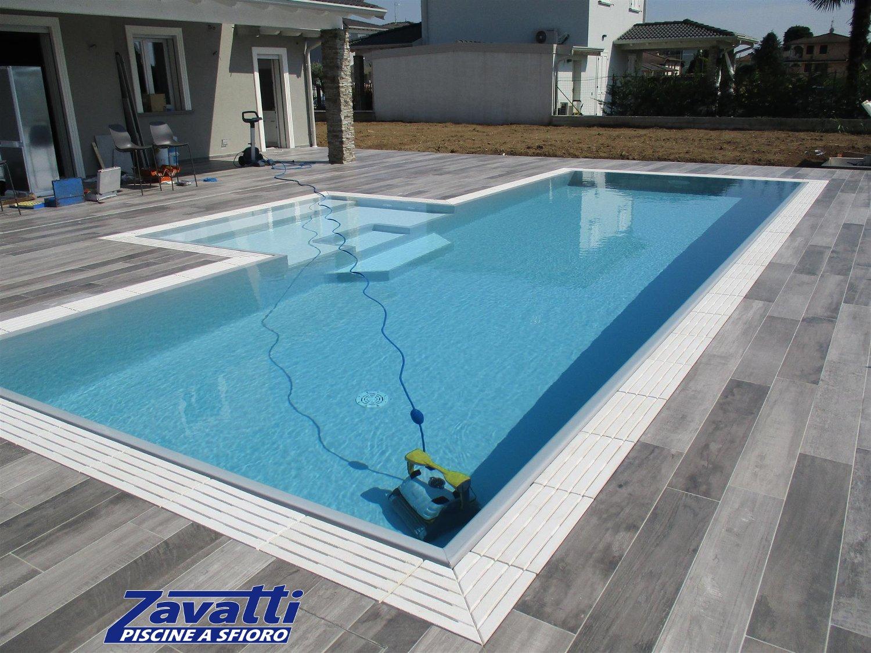 Vista totale piscina a sfioro con griglia in pietra bianca a quattro fessure e rivestimento grigio chiaro. Design in armonia con la pavimentazione che circonda la piscina