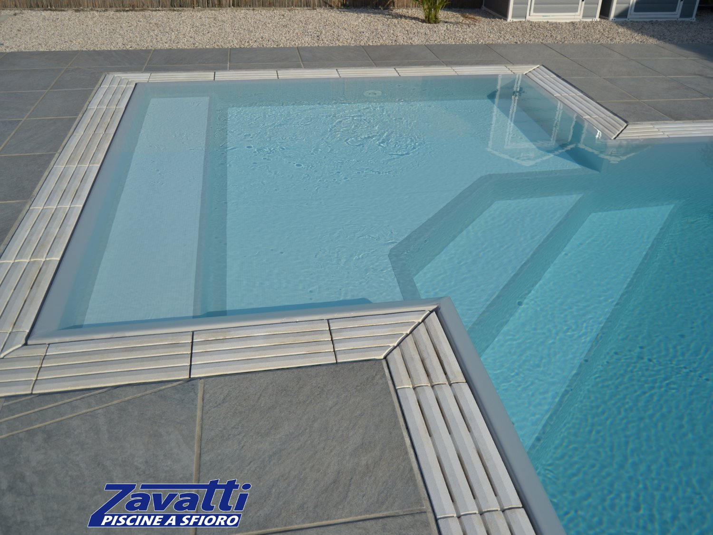 Primo piano spiaggia di una piscina a sfioro con rivestimento grigio e bordo tradizionale con griglia in pietra