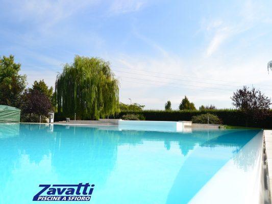 Close up piscina a sfioro Zavatti con rivestimento bianco e bordo a scomparsa