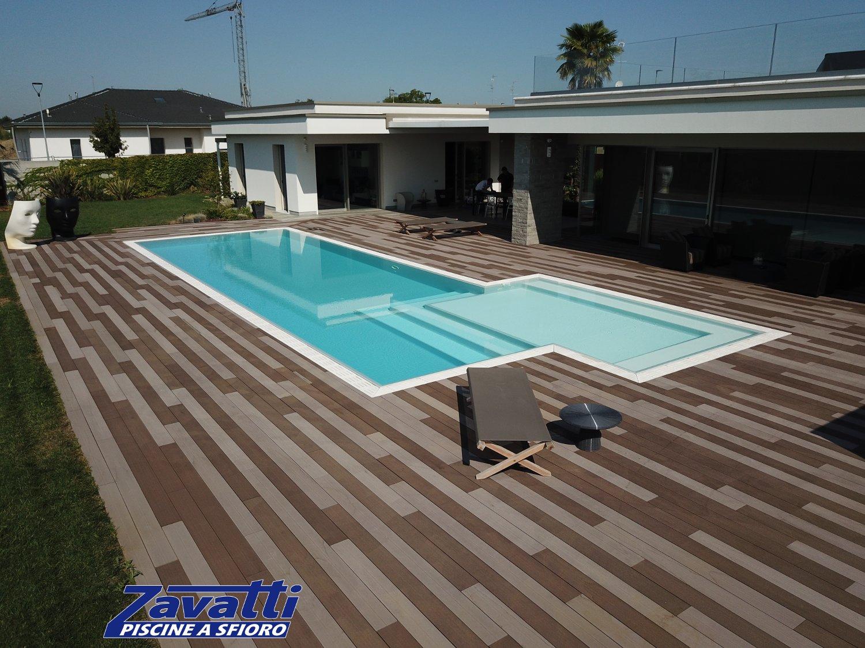 Contrasto cromatico tra la piscina con liner grigio e la pavimentazione circostante dai colori caldi