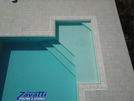 Dettaglio ingresso angolare di una piscina a sfioro con griglia in pietra ricostruita e rivestimento in PVC sabbia