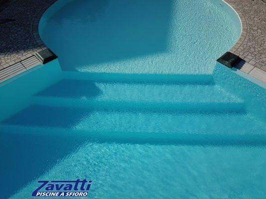 Dettaglio scalini piscina a sfioro con zona relax circolare