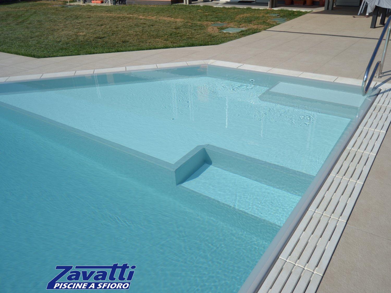 Primo piano bagnasciuga di una piscina a sfioro con rivestimento armato PVC grigio