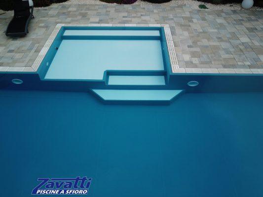 Piscina a sfioro realizzata con rivestimento ad alta pigmentazione blu intenso, in contrasto con gli scalini e la griglia in pietra bianca