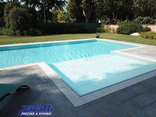 Piscina a sfioro con acqua cristallina grazie al rivestimento chiaro e all'efficiente sistema di filtrazione a sabbia