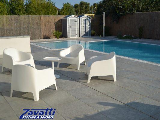Piscina a sfioro con rivestimento grigio e griglia in pietra bianca, per creare continuità tra piscina e ambiente