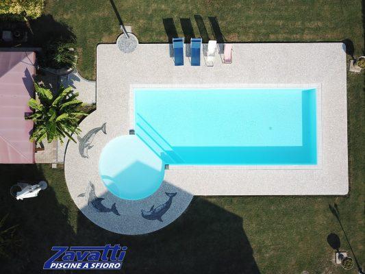 Piscina interrata senza vasca di compenso con rivestimento bianco e spiaggia circolare