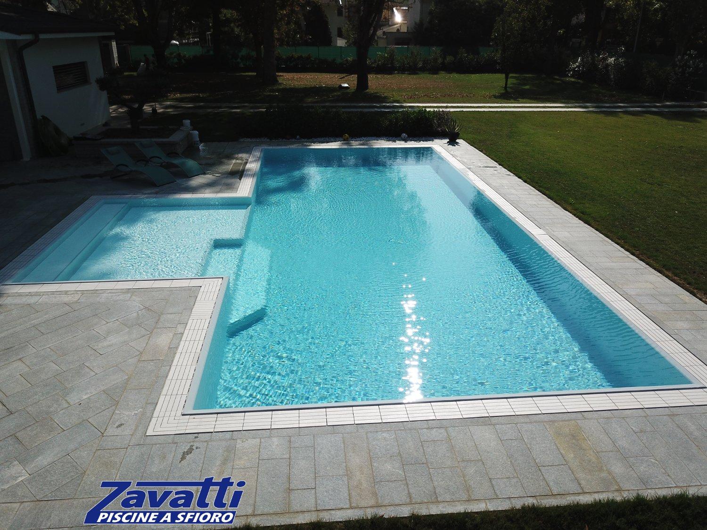 Increspature di una piscina a sfioro realizzata con ampia spiaggia laterale e gradino interno trapezoidale